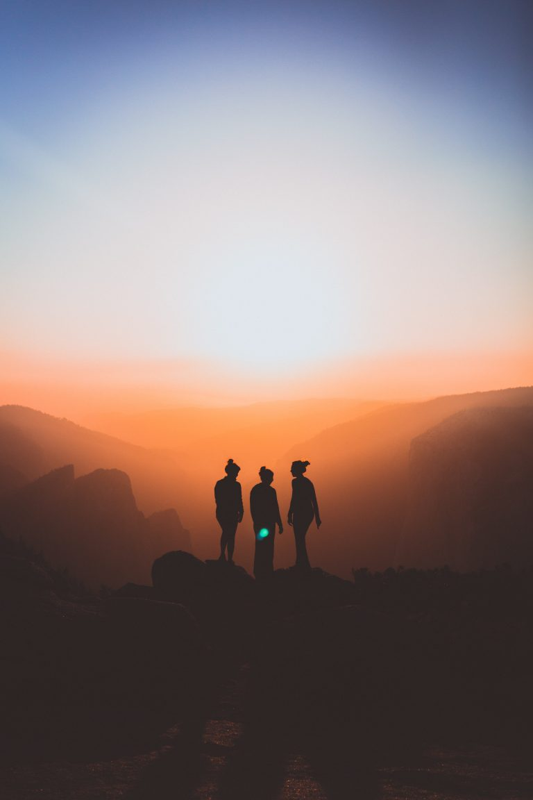 3 persons standing on a mountain